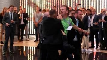 iaa: klimaaktivist stürmt bühne während auftritts von angela merkel