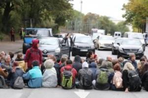 sitzblockaden: aktivist springt nach klimademo auf motorhaube eines autos