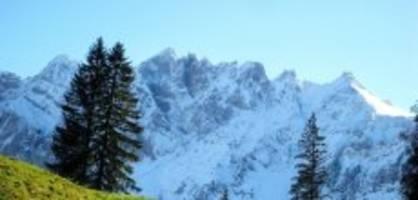 wildhaus: skifahrer lösen neben piste ein schneebrett aus