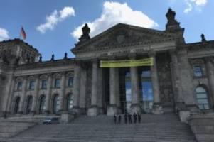 aktion: kohleausstieg - greenpeace-aktivisten klettern auf reichstag