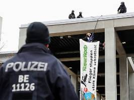 banner entrollt: aktivisten wollen ber-eröffnung stören