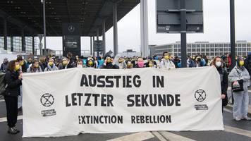 flughafen ber: aktivist klebt sich an flugzeug fest